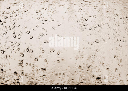 High contrast photo of drops of rain on a window glass with light pale copper orange color - Stock Photo