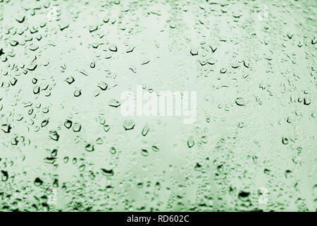 High contrast photo of drops of rain on a window glass with light pale emerald green color - Stock Photo