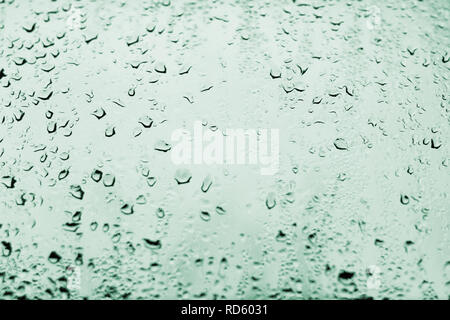 High contrast photo of drops of rain on a window glass with light pale teal green color - Stock Photo