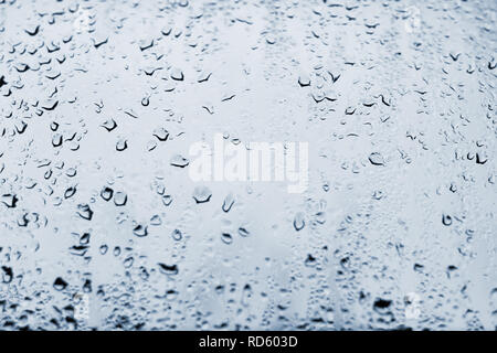 High contrast photo of drops of rain on a window glass with light pale blue color - Stock Photo
