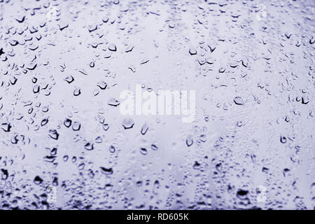 High contrast photo of drops of rain on a window glass with light pale purplish blue color - Stock Photo