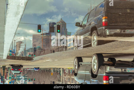 Reflections of a car and city buildings on a large rainwater puddle after a winter storm in downtown Seattle, Washington, United States. - Stock Photo