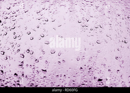 High contrast photo of drops of rain on a window glass with light pale lilac color - Stock Photo