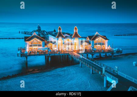 Famous Sellin Seebruecke (Sellin Pier) in beautiful evening twilight at dusk in summer, Ostseebad Sellin tourist resort, Baltic Sea region, Germany - Stock Photo