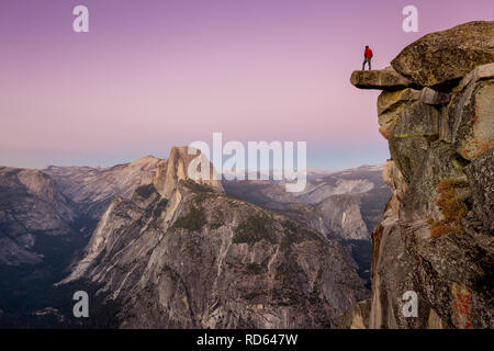 A fearless male hiker is standing on an overhanging rock at Glacier Point enjoying the breathtaking view towards famous Half Dome at sunset, Yosemite - Stock Photo