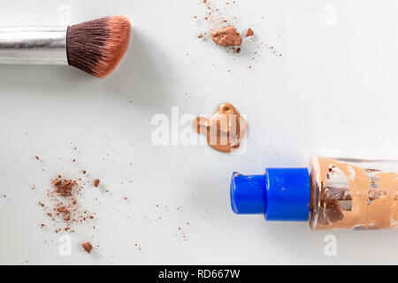 flat lay of makeup showing a makeup brush and glass bottle, surrounded by scattered makeup. - Stock Photo