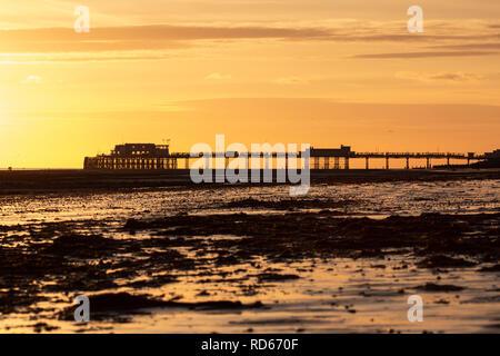 Worthing pier set against an orange sky - Stock Photo