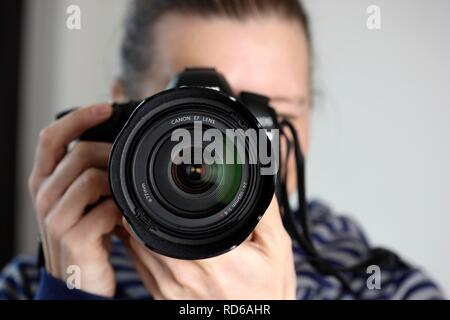 Woman looking through the viewfinder of a digital SLR camera - Stock Photo