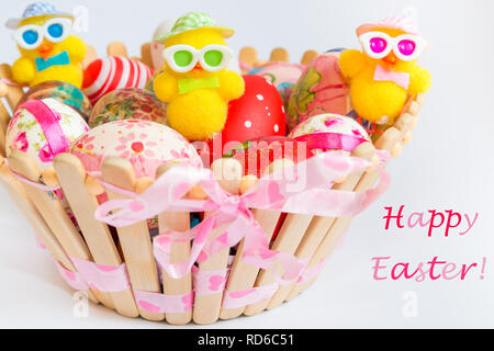 Easter decoration with colorful eggs and funny chicks in wooden basket isolated on white background. Easter holiday concept. - Stock Photo