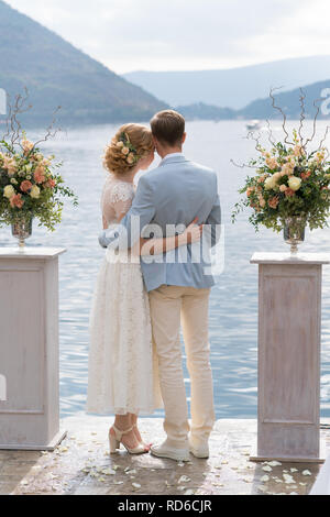 newlywed couple stands embracing against the sea between the stands with flower arrangements after the wedding ceremony - Stock Photo