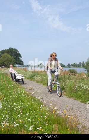 Cyclist on the Elbe dike at Wussegel near Hitzacker, Naturpark Elbufer-Drawehn nature reserve, Lower Saxony, Germany - Stock Photo