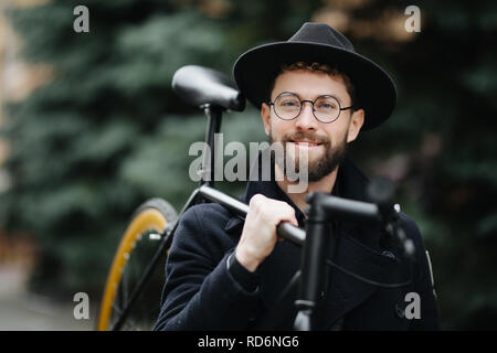 Bearded man with retro bicycle. Low angle view of confident young bearded man carrying his bicycle on shoulder and looking away while walking outdoors