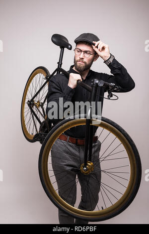 Young bearded handsome man wearing in eyeglasses and hat holding fixed bicycle isolated on white background - Stock Photo