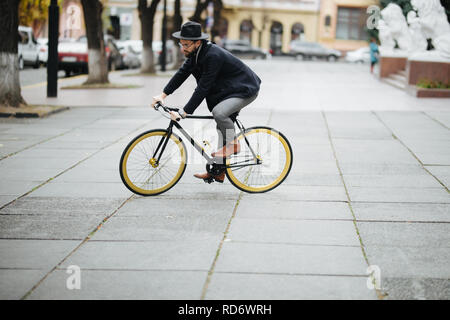 Young bearded man riding bicycle to work on urban street - Stock Photo