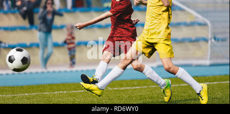 Two Young Soccer Players Kicking Ball on Soccer Field. Soccer Horizontal Background. Youth Junior Athletes in Red and Yellow Soccer Shirts - Stock Photo