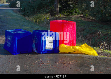 Empty upside down Blue Box recycling bins at curbside with a red bin for plastics and a yellow bag for cardboard. - Stock Photo