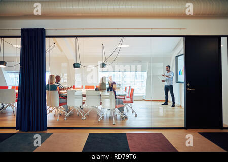 Manager giving a presentation to a diverse group of collegues sitting together around a table inside of a glass office - Stock Photo