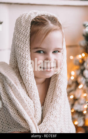 Cute little girl covered in a big plaid or scarf at home - Stock Photo