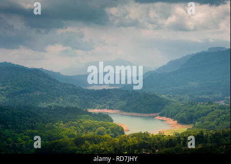 Ramboda, Sri Lanka. Green valley views to lake and distant mountains with stormy sky background - Stock Photo