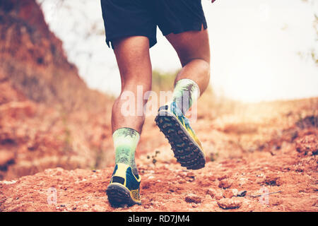 A man Runner of Trail . and Close up of an athlete's feet wearing sports shoes for trail running in the mountains - Stock Photo