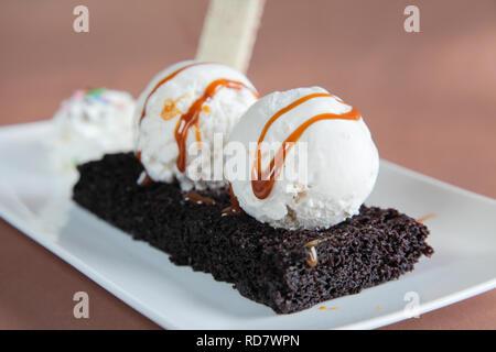 Chocolate Brownie with Vanilla Ice Cream and Syrup - Stock Photo