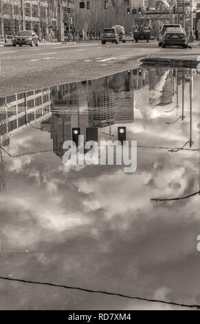 Reflections of  Seattle waterfront city buildings on a large rainwater puddle after a winter storm in downtown Seattle, Washington, United States. - Stock Photo