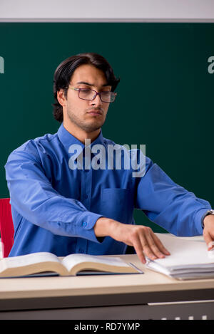 Young male teacher in front of chalkboard - Stock Photo