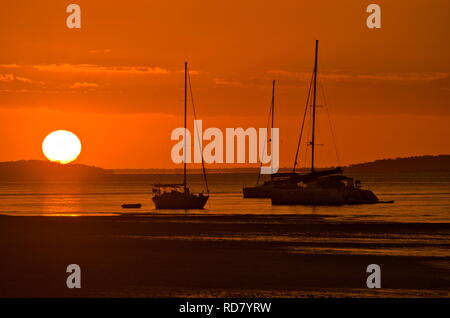 Dramatic red sunset over three yachts docked in harbour on Fraser Island while orange light reflects off ocean and wet sand - Stock Photo