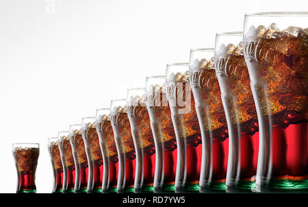 Glasses of Coca Cola with ice, in a row against a white background - Stock Photo