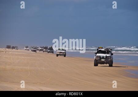 Line of four-wheel drives drive on beach next to choppy ocean