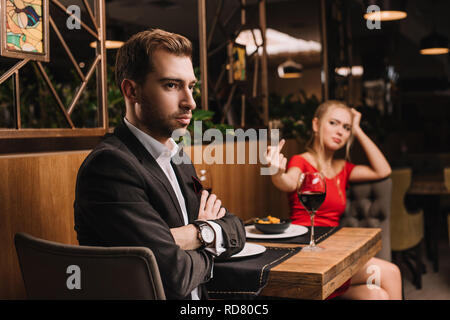 selective focus of offended man sitting with crossed arms while girlfriend showing middle finger during dinner - Stock Photo
