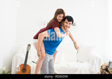 Romantic happy young couple relax at modern home indoors and have fun. Couple hugging and smiling while spending time together. - Stock Photo