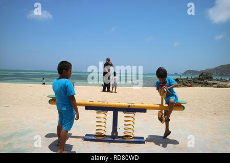 Playing Seesaw in the Mandalika Beach, Lombok, Indonesia - Stock Photo