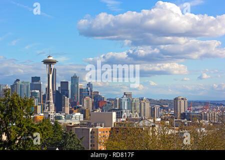 Urban Seattle panorama and distinctive peak of Mount Rainier above the clouds on horizon. - Stock Photo