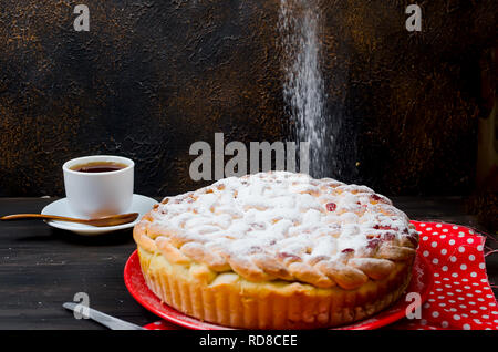 Delicious Homemade cherry Pie dusted with icing sugar on the plate on the dark old wooden table. Making cherry Pie Series, - Stock Photo