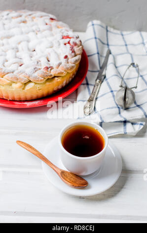 Delicious Homemade cherry Pie dusted with icing sugar on the plate whits cup of tea on the white old wooden table. Making cherry Pie Series, - Stock Photo