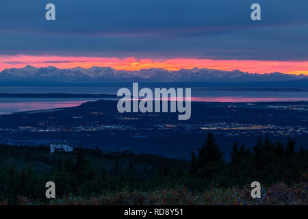 The sun sets behind the Tordrillo Mountains as darkness falls over the city of Anchorage, Alaska - Stock Photo