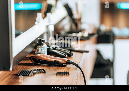 close-up view of electric hair clipper on wooden shelf in beauty salon - Stock Photo