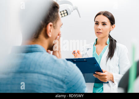 selective focus of female dentist standing with clipboard and talking with african american patient having toothache - Stock Photo