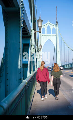 Two young girls with a good fit and long hair walking along the walkway of the gothic arches of the St Johns bridge across the Willamette River - Stock Photo