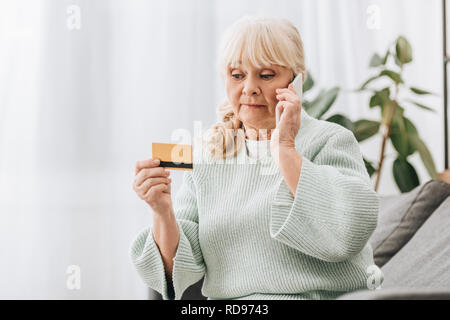 confused senior woman looking at credit card while talking on smartphone - Stock Photo