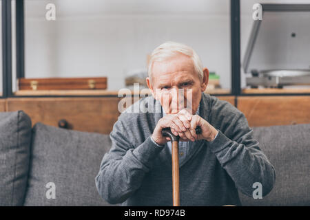 upset retired man with grey hair sitting with walking cane in living room - Stock Photo