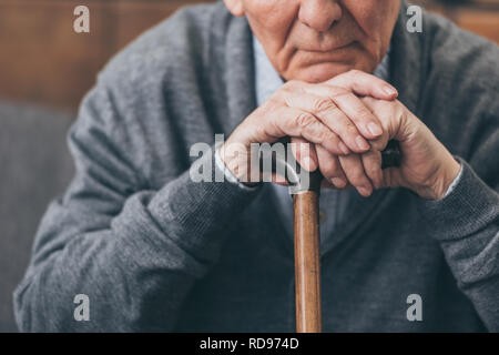 cropped view of upset retired man with walking cane - Stock Photo