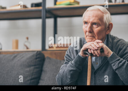 sad retired man with grey hair holding walking cane in living room - Stock Photo