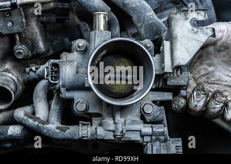 Close-up of the engine, throttle, raditor. Engine breakdown: contaminated throttle of an old car - Stock Photo