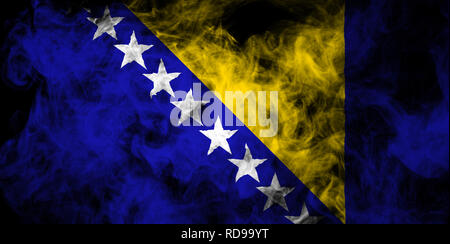 National flag of Bosnia  Herzegovina from thick colored smoke on a black isolated background - Stock Photo
