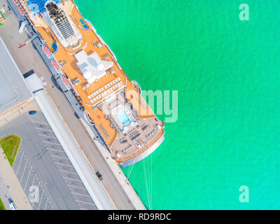 Aerial View by Drone of Cruise ship at harbor. Top view of beautiful large white liner in yacht club. Luxury cruise in sea water. Marina dock. Ship is - Stock Photo