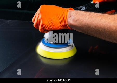 Car polish wax worker hands applying protective tape before polishing. Buffing and polishing car. Car detailing. Man holds a polisher in the hand and  - Stock Photo