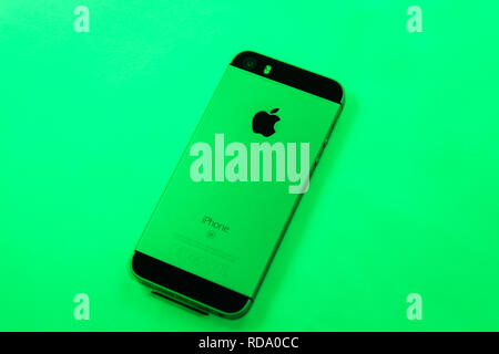 Paris, France - Apr 21, 2016: Newest Apple Computers iPhone SE smartphone after unboxing on green vivid right background featuring - Stock Photo