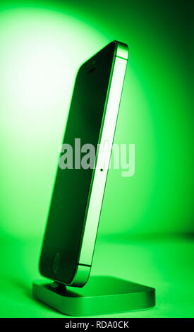 Paris, France - Apr 21, 2016: Hero object of newest Apple Computers iPhone SE smartphone after unboxing on green background featuring new form factor - Stock Photo